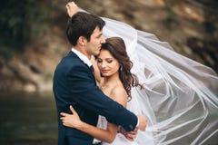 Eleganter leichter stilvoller Bräutigam und Braut nahe Fluss mit Steinen Hochzeitspaare in der Liebe stockbilder