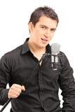 Eleganter männlicher Sänger, der ein Mikrofon hält Lizenzfreie Stockfotografie