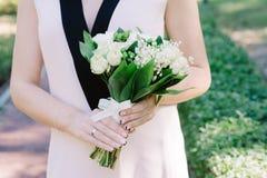 Eleganter Maiglöckchenhochzeitsblumenstrauß in den Händen der Braut Stockbilder