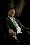 Eleganter Mann, der in einem Stuhl vorbei hält Gewehr sitzt Lizenzfreie Stockfotografie
