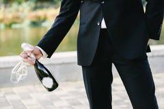 Eleganter Mann, der Gläser und eine Flasche hält lizenzfreie stockbilder