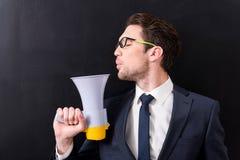 Eleganter Mann in der Klage steht mit Megaphon Stockfoto