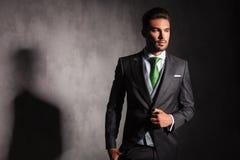 Eleganter Mann in der Smokingsjacke, die seinen Mantel knöpft, schaut weg lizenzfreie stockbilder