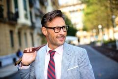 Eleganter Mann, der in Straße mit Tasche auf Schultern geht Lizenzfreie Stockbilder