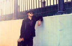 Eleganter Mann in einem Hut, der nahe der Wand steht stockfotografie