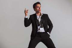 Eleganter Mann im Smoking, das seine Finger und Blinzeln reißt Stockfotos