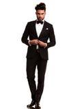 Eleganter Mann im Smoking, das seinen Mantel aufknöpft Stockfotografie