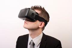 Eleganter, neutraler Mann in einem schwarzen Gesellschaftsanzug, einen Oculus-Risses 3D VR-virtueller Realität tragend Kopfhörer  Lizenzfreies Stockbild