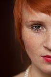 Eleganter Redhead mit Freckles auf braunem Hintergrund stockbilder