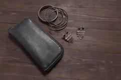 Eleganter Satz: schwarze Geldbörse, silberne Armbänder, silberne Ohrringe, O Stockbild