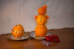 Eleganter Schneemann von den Tangerinen in einer roten Kappe von den Karotten in einer Untertasse und in einer roten Kröte vom gr stockbilder