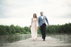 Eleganter stilvoller Bräutigam mit seiner glücklichen herrlichen Brunettebraut auf dem Hintergrund von einem See lizenzfreies stockfoto