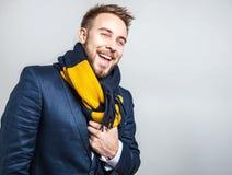 Eleganter u. positiver junger gutaussehender Mann im bunten Schal Mann entfernen irgendjemandes Kleidung Stockfotografie