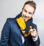 Eleganter u. positiver junger gutaussehender Mann im bunten Schal Mann entfernen irgendjemandes Kleidung Lizenzfreies Stockfoto
