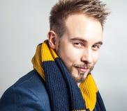 Eleganter u. positiver junger gutaussehender Mann im bunten Schal Mann entfernen irgendjemandes Kleidung Lizenzfreies Stockbild