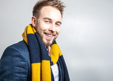 Eleganter u. positiver junger gutaussehender Mann im bunten Schal Mann entfernen irgendjemandes Kleidung Lizenzfreie Stockfotos