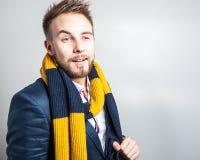 Eleganter u. positiver junger gutaussehender Mann im bunten Schal Mann entfernen irgendjemandes Kleidung Stockfotos