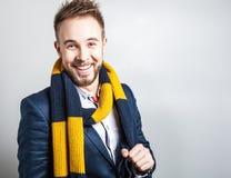 Eleganter u. positiver junger gutaussehender Mann im bunten Schal Mann entfernen irgendjemandes Kleidung Lizenzfreie Stockfotografie