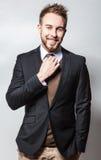 Eleganter u. positiver junger gutaussehender Mann im Kostüm Mann entfernen irgendjemandes Kleidung Stockfotografie