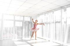 Eleganter weiblicher Balletttänzer im rosa übenden und lächelnden Ballettröckchen Stockfotografie