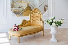 Eleganter Weinleselehnsessel in einem geräumigen Raum mit Wand verzierte Verzierungen und Spiegel bunte Blumen im Vase, der auf s Lizenzfreie Stockbilder