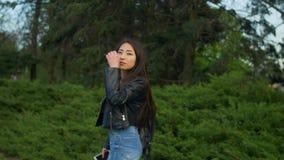 Elegantes asiatisches Mädchen, das im Park zurück lächeln dreht stock footage