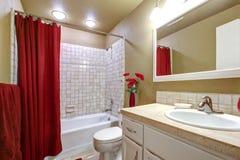 Elegantes beige und rotes Badezimmer mit Wanne und Wanne. Stockfotografie