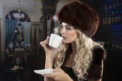 Elegantes blondes Mädchen, das eine Tasse Tee trinkt Lizenzfreie Stockfotografie