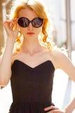 Elegantes blondes Modell im schwarzen Sommerkleid am sonnigen Tag Stockbild