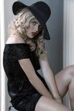 Elegantes gekleidetes Mädchen, das mit einem Hut aufwirft Stockbild