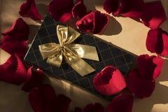 Elegantes Geschenk mit einem goldenen Bogen um rote rosafarbene Blumenblätter stockbilder