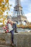 Elegantes Kind auf Damm in Paris, das auf dem Geländer sitzt Stockbild