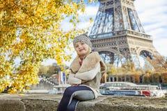 Elegantes Kind, das auf Geländer auf Damm nahe Eiffelturm sitzt Lizenzfreie Stockfotos