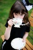 Elegantes Kindmädchen, das eine Teeparty draußen hat Lizenzfreie Stockfotos