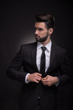 Elegantes Klagenknöpfen des jungen Mannes, seitlich schauend Lizenzfreies Stockbild