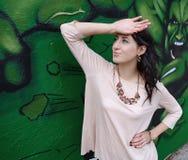 Elegantes Mädchen auf Graffitihintergrund Stockfoto