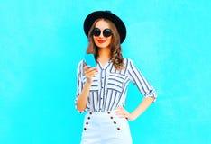 Elegantes Mädchen benutzt einen Smartphone, der einen schwarzen Hut und eine Handtasche trägt Stockfoto