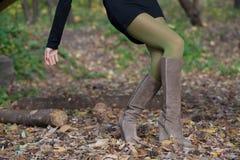 Elegantes Mädchen in den Velourslederstiefeln im Wald gehend Lizenzfreie Stockbilder
