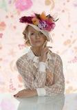 Elegantes Mädchen hinter Tabelle mit Blumenhut und der Hand nahe dem Gesicht Lizenzfreie Stockfotografie