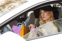 Elegantes Mädchen im Auto mit Einkaufstaschen Stockbilder