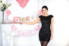 Elegantes Mädchen im schwarzen Kleid, das nahe steht Stockbilder