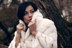 Elegantes Mädchen im weißen Mantel mit hohem Kragen Lizenzfreie Stockfotos
