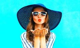 Elegantes Mädchen mit den roten Lippen ist sendet einen Luftkuß im Strohsommer Lizenzfreies Stockfoto
