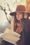 Elegantes Mädchen mit einem Buch im warmen Herbstlicht Stockfotografie