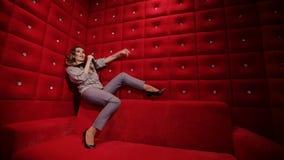 Elegantes Mädchen mit einem Mikrofon-Gesang karaokeof ein rotes Sofa auf einem roten Hintergrund stock video