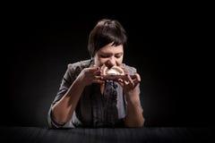 Elegantes Mädchen, das einen Schokoladenkuchen isst Stockbilder