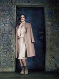 Elegantes Mode-Modell, das den langen Mokkamantel, werfend vor einer Tür trägt auf lizenzfreies stockbild