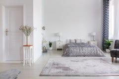 Elegantes New- Yorkartschlafzimmer mit bequemem Bett, wirkliches Foto mit Kopienraum auf der weißen Wand lizenzfreie stockbilder