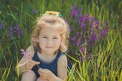 Elegantes rubios lindos del niño de la chica joven vestidos en tejanos visten la presentación en el prado del mayweed salvaje del Fotografía de archivo