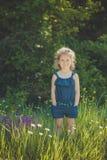 Elegantes rubios lindos del niño de la chica joven vestidos en tejanos visten la presentación en el prado del mayweed salvaje del Foto de archivo